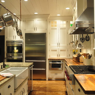 Inspiration for a mid-sized country l-shaped separate kitchen in Louisville with a farmhouse sink, stainless steel appliances, shaker cabinets, wood benchtops, white cabinets, white splashback, ceramic splashback, medium hardwood floors and with island.