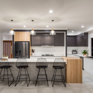 Inspiration for a large contemporary galley kitchen pantry in Other with a drop-in sink, flat-panel cabinets, white cabinets, granite benchtops, white splashback, subway tile splashback, black appliances, ceramic floors, with island, grey floor and white benchtop.