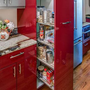 Modelo de cocina comedor en L, minimalista, pequeña, sin isla, con puertas de armario rojas, encimera de granito, salpicadero multicolor, electrodomésticos de acero inoxidable, suelo de madera clara y armarios con paneles lisos