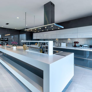 Inspiration for an expansive contemporary l-shaped eat-in kitchen in San Francisco with flat-panel cabinets, grey cabinets, solid surface benchtops, blue splashback, stainless steel appliances, porcelain floors, with island, white floor, white benchtop, an undermount sink and glass sheet splashback.
