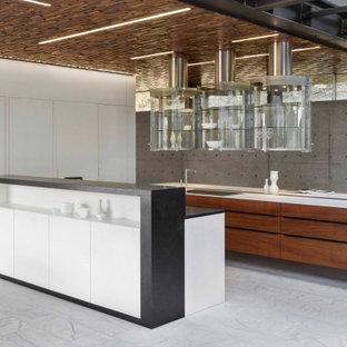 Réalisation d'une très grand cuisine design en L avec un évier encastré, un placard à porte plane, des portes de placard blanches, un électroménager encastrable, 2 îlots, un sol gris et un plan de travail blanc.