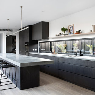 Photo of a modern galley kitchen in Melbourne with a double-bowl sink, concrete benchtops, light hardwood floors, with island, flat-panel cabinets, black cabinets, window splashback, black appliances, beige floor and grey benchtop.