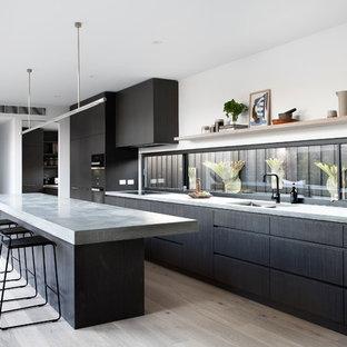Inspiration för ett funkis grå grått parallellkök, med en dubbel diskho, bänkskiva i betong, ljust trägolv, en köksö, släta luckor, svarta skåp, fönster som stänkskydd, svarta vitvaror och beiget golv