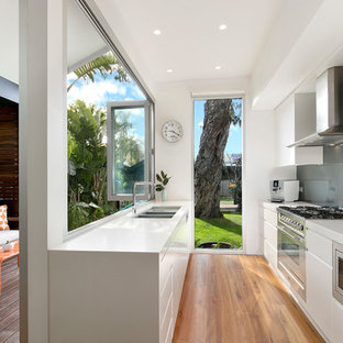 Design ideas for a contemporary galley eat-in kitchen in Sydney with a double-bowl sink, white cabinets, glass sheet splashback, stainless steel appliances, flat-panel cabinets, medium hardwood floors, no island, brown floor, grey splashback and white benchtop.
