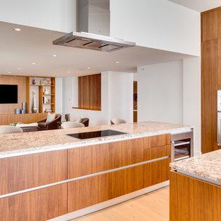 Offene, Große Moderne Küche in L-Form mit Unterbauwaschbecken, flächenbündigen Schrankfronten, hellbraunen Holzschränken, Granit-Arbeitsplatte, Rückwand aus Spiegelfliesen, Küchengeräten aus Edelstahl, hellem Holzboden, Kücheninsel, beigem Boden und bunter Arbeitsplatte in Miami