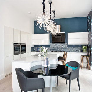 Mid-sized contemporary open plan kitchen in Other with an undermount sink, flat-panel cabinets, white cabinets, concrete benchtops, blue splashback, panelled appliances, light hardwood floors and with island.
