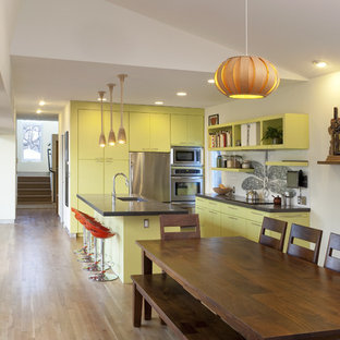 This is an example of a contemporary eat-in kitchen in Austin with stainless steel appliances, concrete benchtops, an undermount sink, flat-panel cabinets and green cabinets.