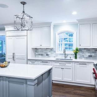 Bild på ett stort vintage vit vitt kök, med en undermonterad diskho, luckor med profilerade fronter, vita skåp, bänkskiva i kvarts, grått stänkskydd, stänkskydd i glaskakel, integrerade vitvaror, mellanmörkt trägolv och en köksö
