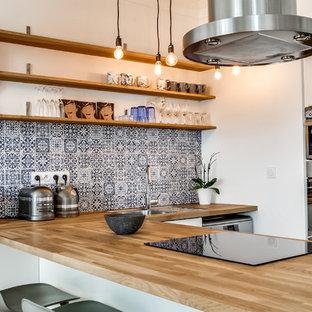 Idée de décoration pour une cuisine ouverte design en U avec un évier posé, un placard sans porte, un plan de travail en bois, une crédence multicolore, une crédence en carreau de ciment, un électroménager en acier inoxydable et une péninsule.