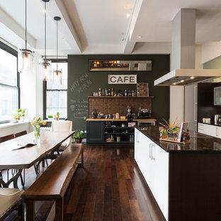 ニューヨークのコンテンポラリースタイルのおしゃれなキッチン (フラットパネル扉のキャビネット、白いキャビネット、濃色無垢フローリング、シルバーの調理設備の、アンダーカウンターシンク) の写真