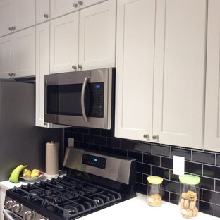 Photo of a small modern galley kitchen pantry in New York with a submerged sink, recessed-panel cabinets, white cabinets, black splashback, metro tiled splashback, stainless steel appliances, plywood flooring, an island, beige floors and quartz worktops.