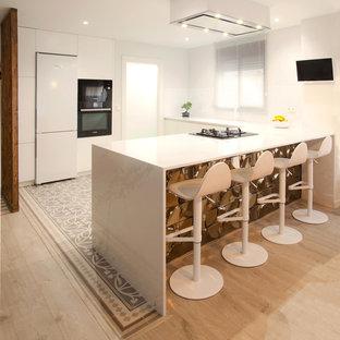 Diseño de cocina en U, actual, con encimera de cuarzo compacto, península, encimeras blancas, armarios con paneles lisos, puertas de armario blancas, salpicadero blanco, electrodomésticos negros y suelo gris