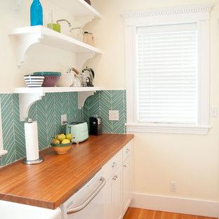 ボストンの中くらいのミッドセンチュリースタイルのおしゃれなキッチン (エプロンフロントシンク、シェーカースタイル扉のキャビネット、白いキャビネット、木材カウンター、青いキッチンパネル、ガラスタイルのキッチンパネル、白い調理設備、無垢フローリング) の写真