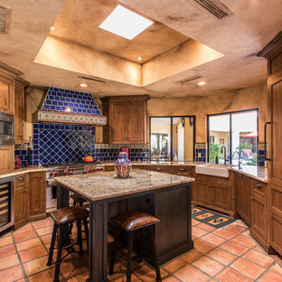 Southwestern kitchen ideas - Example of a southwest u-shaped terra-cotta floor and red floor kitchen design in Phoenix with a farmhouse sink, shaker cabinets, medium tone wood cabinets, blue backsplash, ceramic backsplash, stainless steel appliances, an island and beige countertops