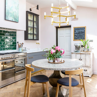 Inspiration for a romantic single-wall kitchen/diner in Gloucestershire with flat-panel cabinets, grey cabinets, marble worktops, green splashback, metro tiled splashback, stainless steel appliances, light hardwood flooring, no island, beige floors and white worktops.