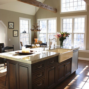 Photo of a mid-sized traditional l-shaped eat-in kitchen in Philadelphia with a farmhouse sink, raised-panel cabinets, soapstone benchtops, grey splashback, stone tile splashback, dark hardwood floors and with island.