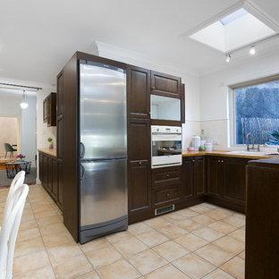 シドニーのヴィクトリアン調のおしゃれなキッチン (ドロップインシンク、レイズドパネル扉のキャビネット、濃色木目調キャビネット、白いキッチンパネル、サブウェイタイルのキッチンパネル、白い調理設備、スレートの床、アイランドなし、ベージュの床、茶色いキッチンカウンター) の写真