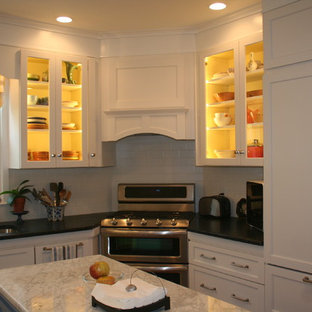 Design ideas for a small eclectic l-shaped eat-in kitchen in Providence with an undermount sink, shaker cabinets, white cabinets, soapstone benchtops, white splashback, ceramic splashback, panelled appliances, light hardwood floors and with island.