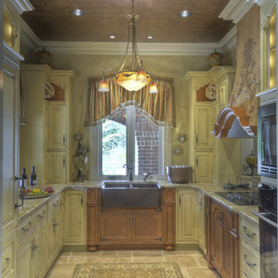Mid-sized french country enclosed kitchen ideas - Mid-sized french country u-shaped travertine floor and beige floor enclosed kitchen photo in Philadelphia with a farmhouse sink, raised-panel cabinets, light wood cabinets, granite countertops, paneled appliances and no island