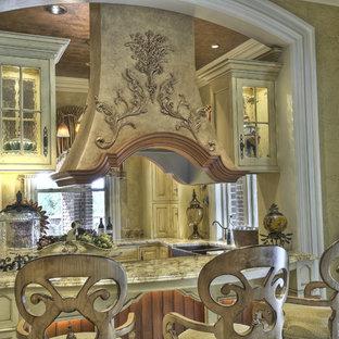 Идея дизайна: отдельная, п-образная кухня среднего размера в средиземноморском стиле с раковиной в стиле кантри, фасадами с выступающей филенкой, светлыми деревянными фасадами, столешницей из гранита, техникой под мебельный фасад, полом из травертина и бежевым полом без острова