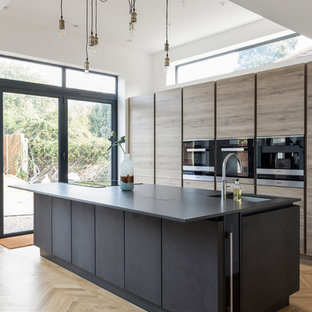 Contemporary galley kitchen in Other with a submerged sink, flat-panel cabinets, medium wood cabinets, stainless steel appliances, medium hardwood flooring, an island and brown floors.
