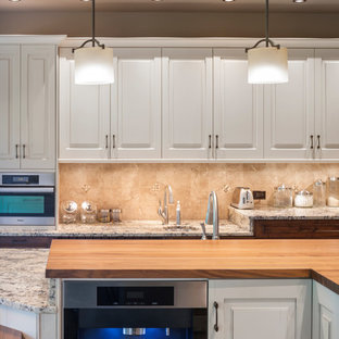 Design ideas for a large contemporary l-shaped kitchen in Kansas City with a submerged sink, recessed-panel cabinets, white cabinets, granite worktops, beige splashback, travertine splashback, integrated appliances, dark hardwood flooring, an island, brown floors and multicoloured worktops.