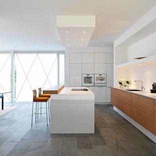Cette photo montre une cuisine américaine parallèle moderne avec un placard à porte plane, des portes de placard en bois brun, un électroménager blanc et un sol en ardoise.