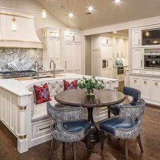 Inspiration för ett stort vintage vit vitt kök, med en undermonterad diskho, luckor med infälld panel, vita skåp, bänkskiva i kvartsit, grått stänkskydd, stänkskydd i marmor, integrerade vitvaror, mörkt trägolv, en köksö och brunt golv