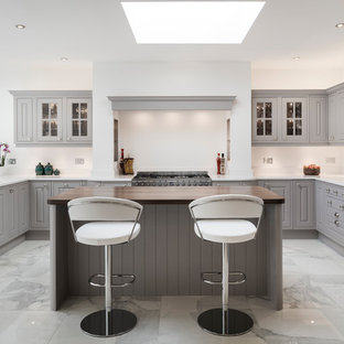 This is an example of a medium sized traditional u-shaped kitchen in Other with grey cabinets, quartz worktops, stainless steel appliances, marble flooring, an island, white worktops, raised-panel cabinets, white splashback and white floors.