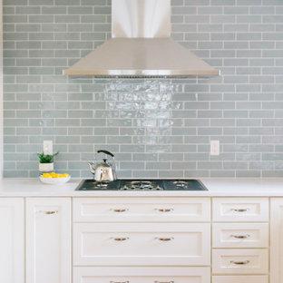 Klassisk inredning av ett litet vit vitt kök, med en undermonterad diskho, skåp i shakerstil, vita skåp, bänkskiva i kvarts, blått stänkskydd, stänkskydd i keramik, rostfria vitvaror, mellanmörkt trägolv, en halv köksö och rött golv