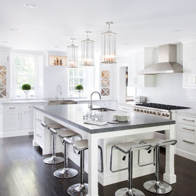 Transitional kitchen photo in New York with a farmhouse sink, shaker cabinets, white cabinets, concrete countertops, white backsplash, mosaic tile backsplash and stainless steel appliances