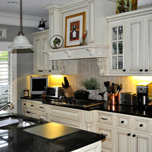 Mid-sized traditional enclosed kitchen remodeling - Example of a mid-sized classic galley dark wood floor enclosed kitchen design in Atlanta with a double-bowl sink, raised-panel cabinets, white cabinets, quartz countertops, beige backsplash, ceramic backsplash, stainless steel appliances and an island
