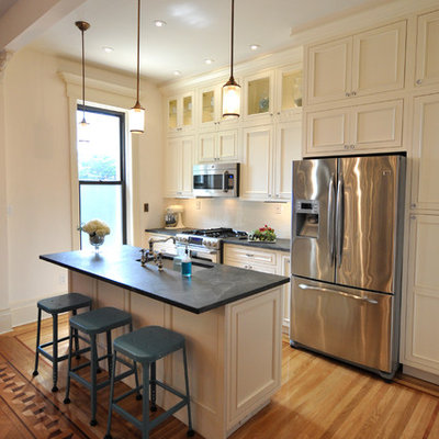Kitchen - traditional galley kitchen idea in New York with recessed-panel cabinets, stainless steel appliances, an undermount sink, beige cabinets and soapstone countertops