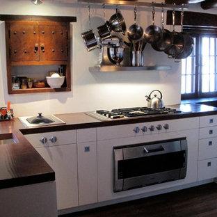 アルバカーキの中サイズのサンタフェスタイルのおしゃれなキッチン (アンダーカウンターシンク、フラットパネル扉のキャビネット、白いキャビネット、人工大理石カウンター、メタリックのキッチンパネル、メタルタイルのキッチンパネル、シルバーの調理設備の、無垢フローリング、茶色い床) の写真