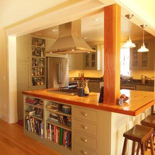 Modelo de cocina comedor en U, contemporánea, de tamaño medio, con fregadero sobremueble, armarios estilo shaker, puertas de armario verdes, electrodomésticos de acero inoxidable, suelo de madera clara, una isla y encimera de madera