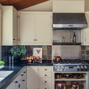 Large midcentury l-shaped eat-in kitchen in Portland with a double-bowl sink, flat-panel cabinets, beige cabinets, granite benchtops, multi-coloured splashback, slate splashback, stainless steel appliances, slate floors, with island, brown floor and black benchtop.