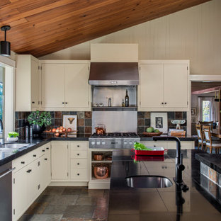 Large midcentury l-shaped kitchen in Portland with a double-bowl sink, flat-panel cabinets, beige cabinets, granite benchtops, multi-coloured splashback, slate splashback, stainless steel appliances, slate floors, with island, brown floor, black benchtop and wood.