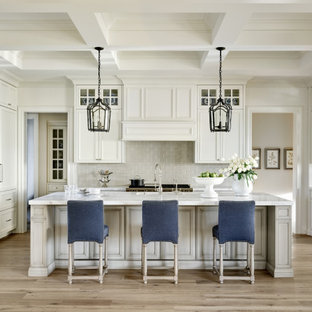 Photo of a large mediterranean u-shaped kitchen in Phoenix with an undermount sink, recessed-panel cabinets, white cabinets, grey splashback, panelled appliances, medium hardwood floors, with island, beige floor, grey benchtop and coffered.