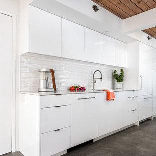 Zweizeilige, Kleine Retro Wohnküche mit Waschbecken, flächenbündigen Schrankfronten, weißen Schränken, Quarzwerkstein-Arbeitsplatte, Küchenrückwand in Weiß, Rückwand aus Keramikfliesen, Elektrogeräten mit Frontblende, Betonboden und Kücheninsel in Portland
