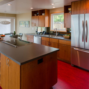 Photo of a mid-sized midcentury galley kitchen in Seattle with flat-panel cabinets, medium wood cabinets, stainless steel appliances, mirror splashback, an undermount sink, with island, solid surface benchtops, linoleum floors and red floor.