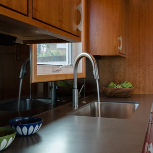 Example of a mid-sized 1950s l-shaped linoleum floor eat-in kitchen design in Seattle with a single-bowl sink, flat-panel cabinets, medium tone wood cabinets, solid surface countertops, mirror backsplash, stainless steel appliances and an island