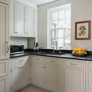 Design ideas for a small classic u-shaped kitchen in New York with a submerged sink, shaker cabinets, beige cabinets, soapstone worktops, beige splashback, limestone splashback, integrated appliances, limestone flooring and black worktops.
