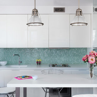 Small contemporary eat-in kitchen pictures - Small trendy single-wall eat-in kitchen photo in New York with white cabinets, blue backsplash, a peninsula, white countertops, an integrated sink and flat-panel cabinets