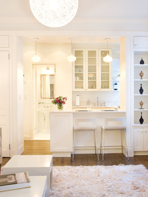example of a small trendy u shaped light wood floor and brown floor eat - All White Kitchen