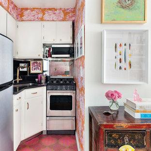 Foto de cocina bohemia, pequeña, abierta, sin isla, con fregadero bajoencimera, armarios con paneles lisos, puertas de armario blancas, salpicadero negro, electrodomésticos de acero inoxidable, suelo rosa y encimeras negras