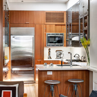 ニューヨーク, NYの小さいトロピカルスタイルのおしゃれなペニンシュラキッチン (フラットパネル扉のキャビネット、中間色木目調キャビネット) の写真