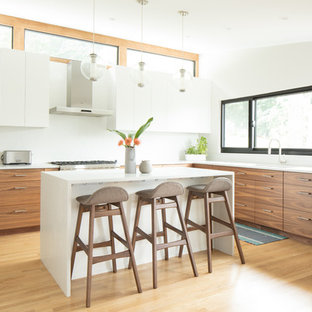 Contemporary kitchen photos - Inspiration for a contemporary l-shaped light wood floor and beige floor kitchen remodel in New York with an undermount sink, flat-panel cabinets, white cabinets, white backsplash, stainless steel appliances and an island