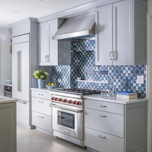 Photo of a large transitional galley kitchen in New York with an undermount sink, quartzite benchtops, blue splashback, panelled appliances, porcelain floors, grey floor, white benchtop, recessed-panel cabinets, grey cabinets and cement tile splashback.