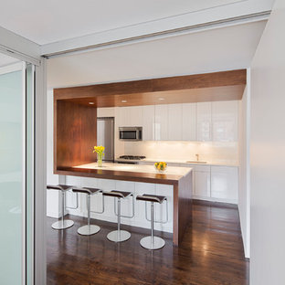 Inspiration for a mid-sized modern galley eat-in kitchen in New York with an undermount sink, flat-panel cabinets, white cabinets, recycled glass benchtops, white splashback, glass sheet splashback, stainless steel appliances, dark hardwood floors, a peninsula and brown floor.