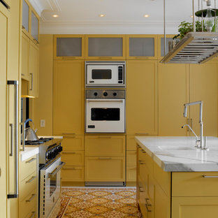 Inspiration for a contemporary galley kitchen in New York with yellow cabinets, white appliances, shaker cabinets, a single-bowl sink and multi-coloured floor.